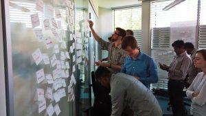 Mehrere Mitarbeiter vor einer Wand mit Post-Its